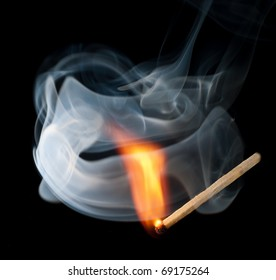 A burning match into the smoke on a black background