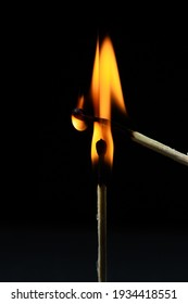Burning match on a black background. A match sets fire to another match against a dark background. Burning in the dark
