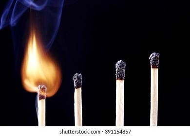 Burning match in a row of match sticks