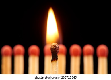 Burning match standing in front of defocused set of eight red wooden matches, isolated on black background