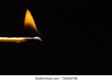 Burning match stick in the left corner of the frame on a black background