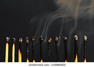 burning Matches in a row in front of a black background