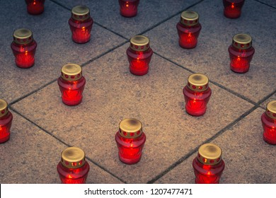 Burning Memorial Red Lantern Candles on granite slabs during Hallowmas and All Saints day. Red lantern light.