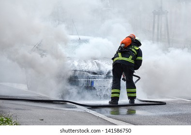 Burning motor vehicle been put out by fireman in protective clothing