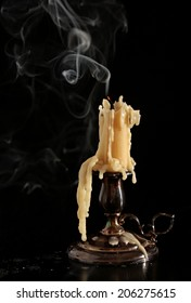 burning old candle vintage bronze candlestick. On a black background. The smoke.