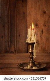 burning old candle vintage bronze candlestick on wooden background.