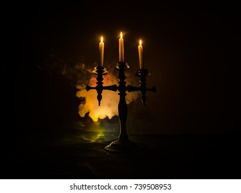 burning old candle vintage wooden candlestick. on dark toned foggy Background. Halloween horror theme