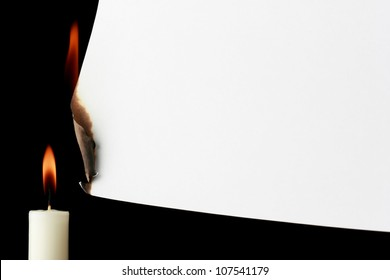 Burning paper with candle on a black background