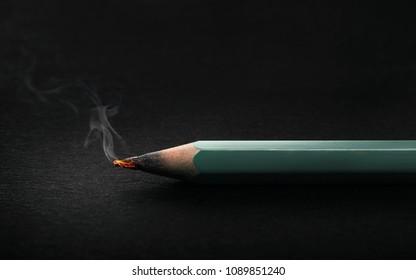 Burning pencil glowing on dark background