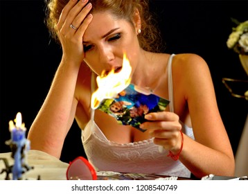 Burning photography kissing newlywed . Wedding bride sitting table. Quarrel during honeymoon. Wedding memories. Couple break up. Woman burns photos of ex-boyfriend.
