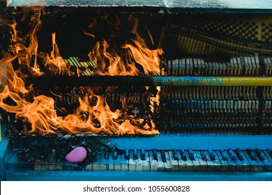 Burning piano, musical style, grunge instrument. Pop music, melody, rhapsody, looting. Fire, art, Halloween, trash, bonfire. Piano on fire, keyboard, smoke. Rock concert, jazz, fireplace, destruction.