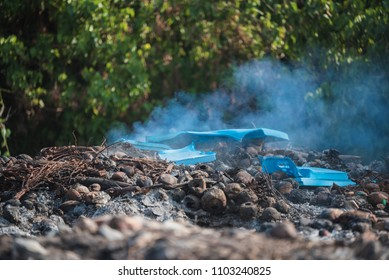 Burning plastic at open dump with blue smokes