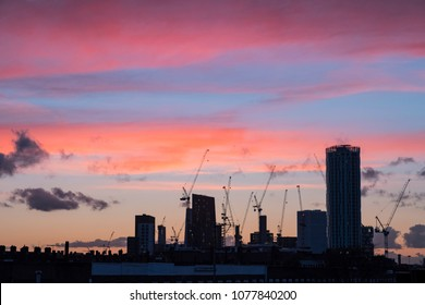 Burning purple sky at sunset over the silhouette of London skyline towers and cranes