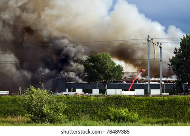 Burning recycling factory with heavy smoke and fire fighters trying to control the fire