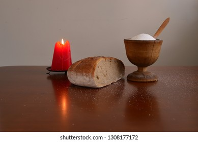 Burning red candle with bread and salt still life.
