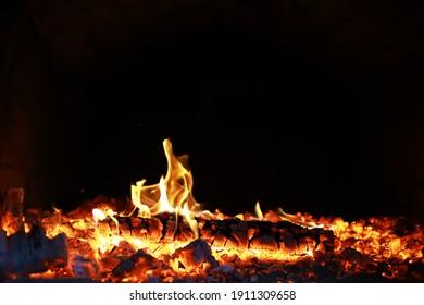 Brennende rote, heiße Funken fliegen aus dem großen Feuer. Schöner abstrakter Hintergrund zum Thema Feuer. Brennende Kohlen, flammende Teilchen, die auf schwarzem Hintergrund abfliegen.
