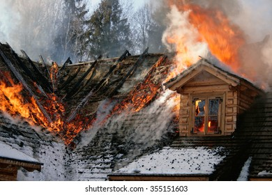 Burning roof of wooden cottage, roof in the flames, trees in the background.