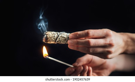 Burning a sage smudge stick for smudging or space cleansing ceremony, black background
