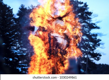 A burning scarecrow is in the park. Shrovetide, traditional event symbolizing spring beginning.