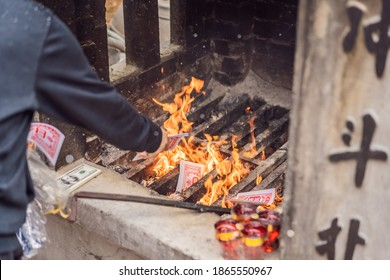 Burning the silver and gold fake money paper for Chinese dead people ancestors. Joss paper money burning metal bucket dead in Chinese new year