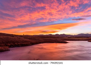 Burning Sky Over A Frozen Lake - Bright red sunset sky over a frozen mountain lake. Bear Creek Park, Denver-Lakewood, Colorado, USA.