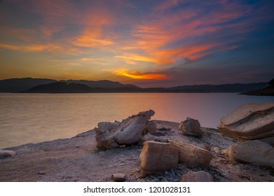 burning sky with rocks on the foreground at the wadas lintang lake