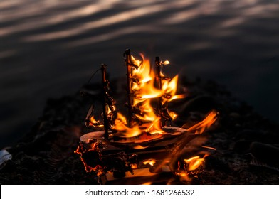 burning small boat standing near the water