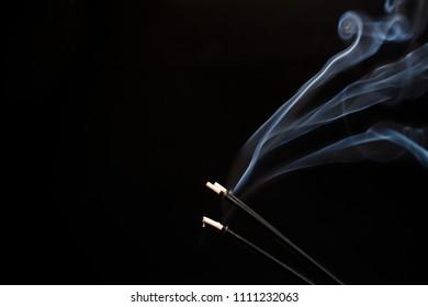 burning and smoking sandalwood sticks closeup on a dark background