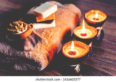 Burning spa aroma candles in coconut shell, handmade soap, towel and washcloth, spa concept background