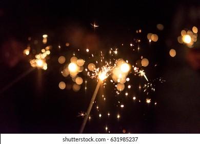 Burning sparkler, abstract blur background.