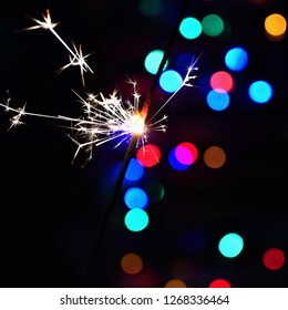 Burning sparkler with beautiful colorful background. Concept for Christmas and Happy New Year.