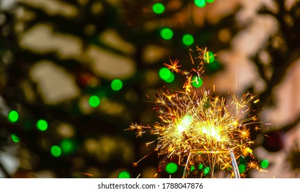 Burning sparklers in a glass against blurred background with green bokeh orbs