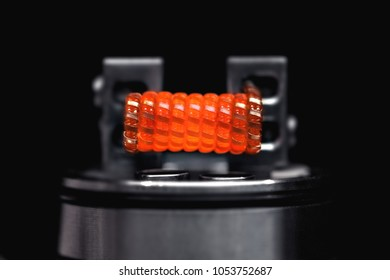 Burning staple staggered fused clapton coil in rebuildable dripping atomizer over dark background