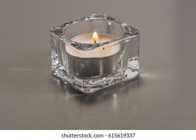 Burning tea candle on a silver background