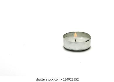 Burning Tea Light Candle Isolated on White