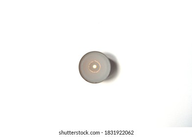 Burning tea light candle on white top view