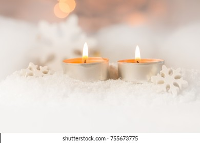 burning tea-lights in snow with soft  background