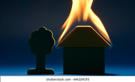 Burning toy house in a dark