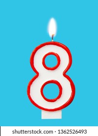 Burning wax candle for a birthday cake in the form of number eight. Blue background