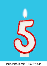 Burning wax candle for a birthday cake in the form of number five. Blue background