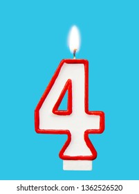 Burning wax candle for a birthday cake in the form of number four. Blue background