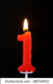 Burning wax candle as number one on black background