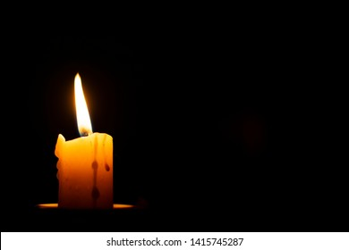 burning wax candle on a black background and a blank place for inscriptions