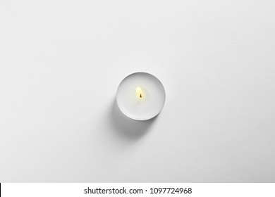 Burning wax candle on white background, top view