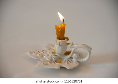 The burning wax candle in a porcelain candlestick