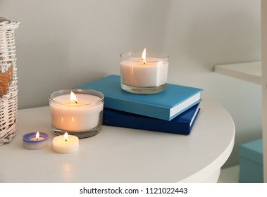 Burning wax candles with books on table indoors