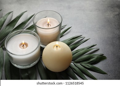 Burning wax candles and tropic leaf on table