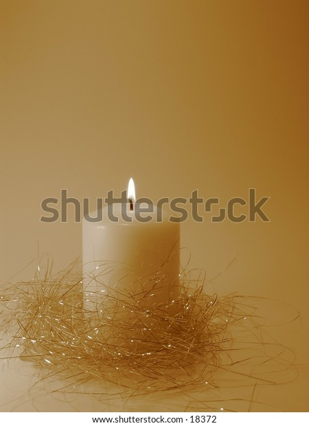 A burning white candle in sepia tone.