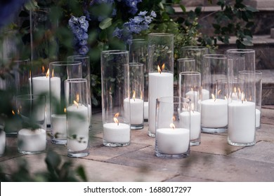 Burning white candles in glass vases on the floor near greenery and purple flowers. The cozy decor of the wedding ceremony.