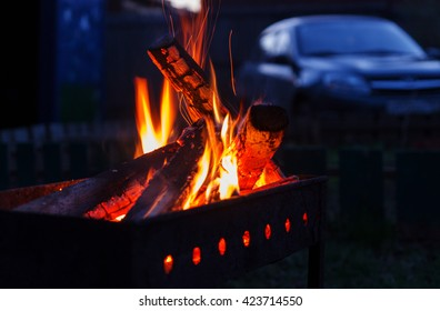 Burning wood in a brazier and a car in the background